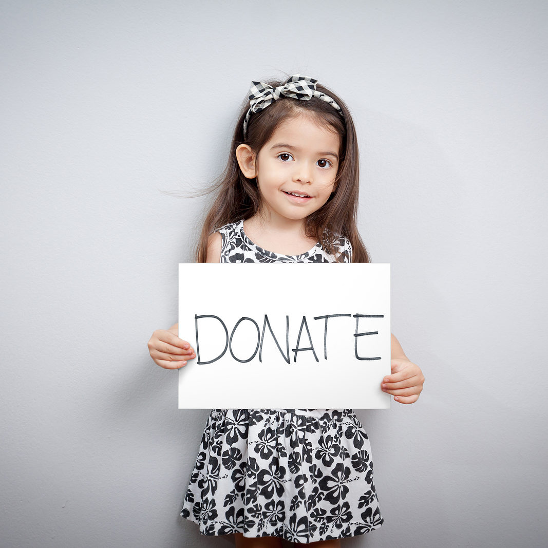 little cute girl with handwriting text donations on white paper. helping, giving , donate and donation concept